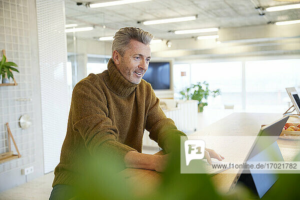 Smiling man using digital tablet while sitting at home