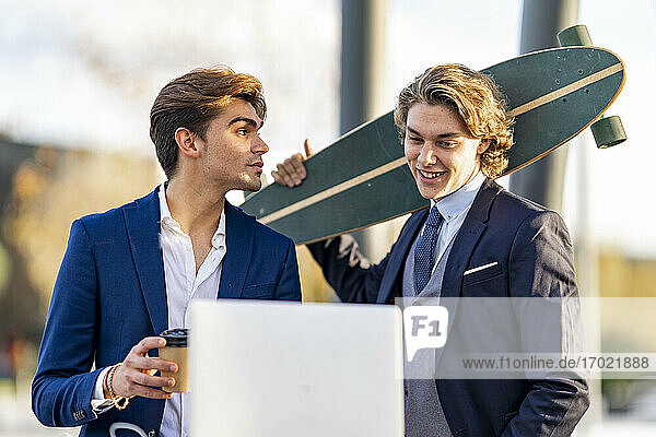 Male entrepreneur looking at colleague carrying skateboard in sunlight