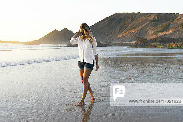 Mid adult woman looking down while walking in water at beach