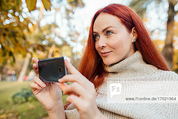 Close-up of beautiful woman photographing with mobile phone in park