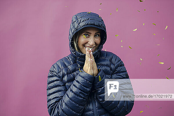 Lächelnde Frau mit gefalteten Händen  stehend gegen
