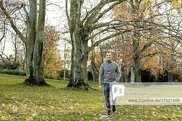 Lächelnder Mann  der im Gras vor Bäumen in einem öffentlichen Park spazieren geht