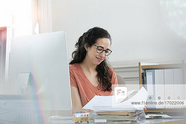 Smiling businesswoman reading document while working in office cabin