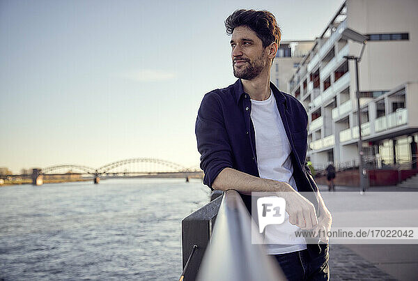 Smiling businessman looking away while standing with hand in pocket on railing