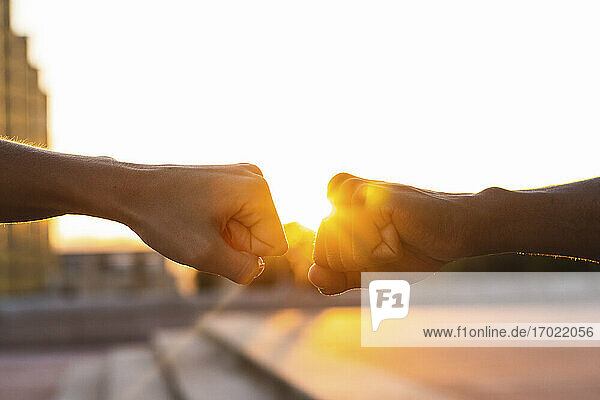 Hands of friends giving fist bump to each other against clear sky during sunset