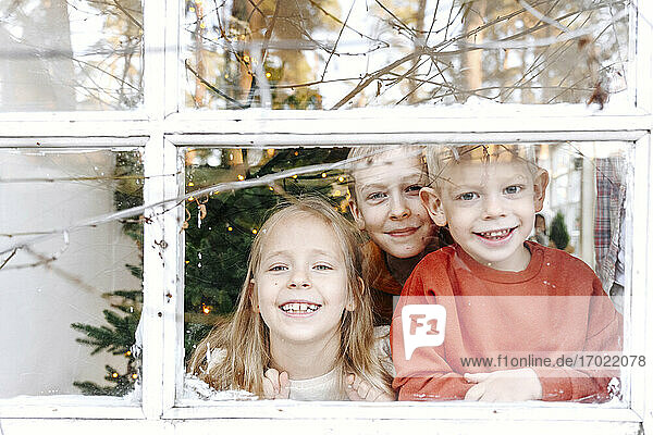 Smiling siblings looking through window from home
