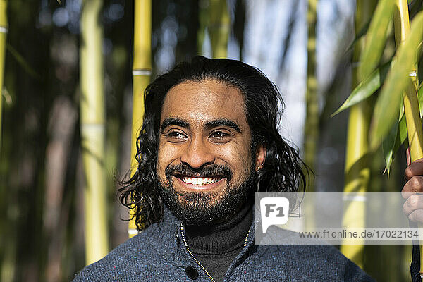 Close-up of smiling bearded young man looking away against bamboo trees