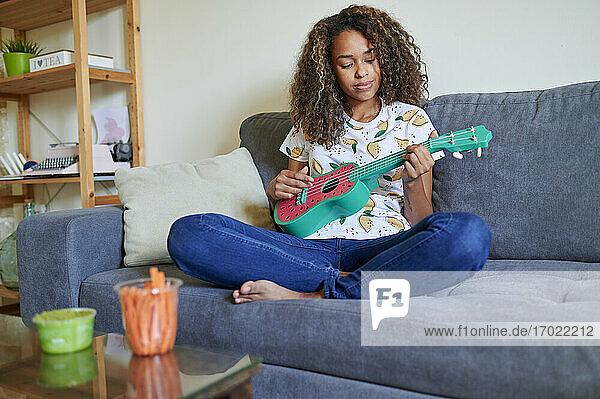 Junge Frau spielt Ukulele zu Hause Junge Frau spielt Ukulele zu Hause