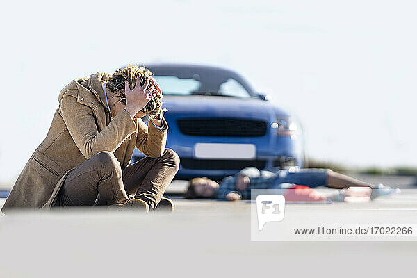 Desperate young man sitting on ground with boy in background lying by car after accident