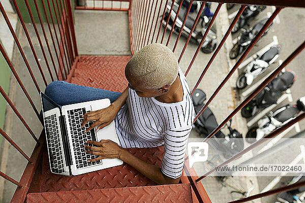 Frau sitzt auf einer Außentreppe und benutzt einen Laptop Frau sitzt auf einer Außentreppe und benutzt einen Laptop