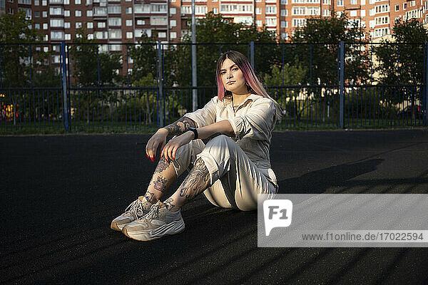 Modische junge Frau mit Tattoo auf einem Sportplatz Modische junge Frau mit Tattoo auf einem Sportplatz