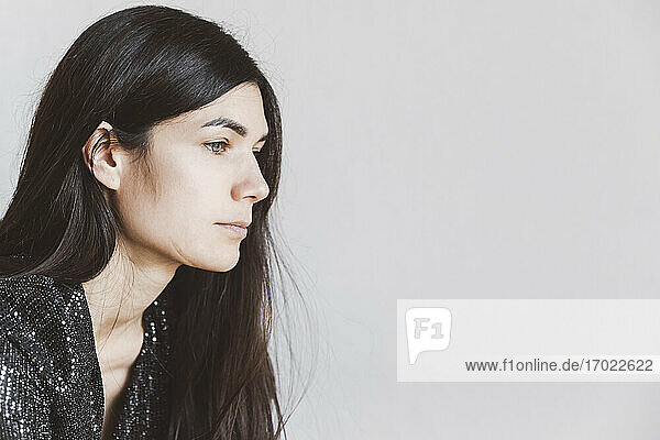 Woman looking away while sitting against white wall at home