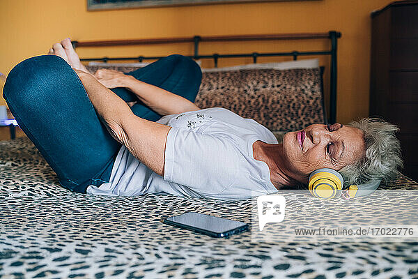 Senior woman relaxing on bed  listening to headphones