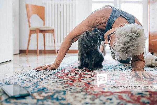 Senior woman with pet cat on floor
