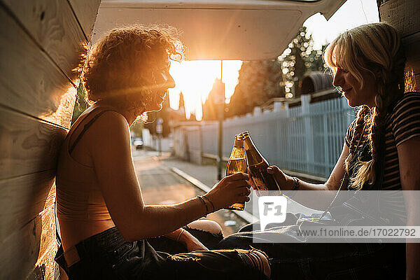 Young female couple toasting with beer bottles in back of van