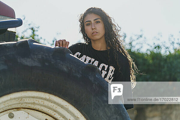 Young woman behind tractor tyre