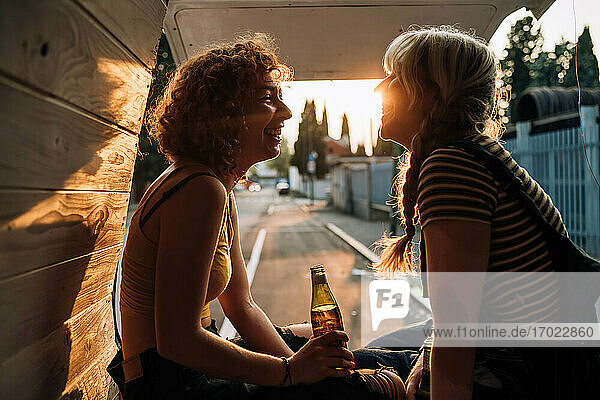Young female couple having a beer in the back of their van