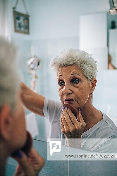 Senior woman looking in mirror  applying makeup