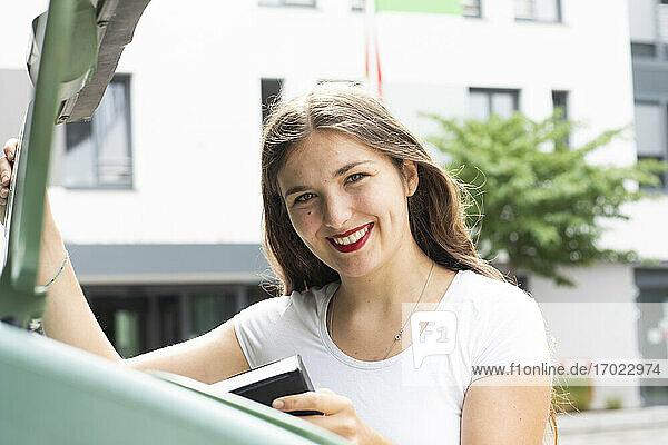Young woman using recycling bin