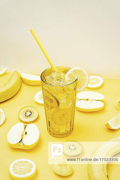 Verschiedene frische Früchte und ein Glas Cocktail mit Eis und Trinkhalm