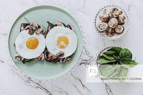 Toasts mit Spiegeleiern  Pilzen und Spinat auf Marmortisch