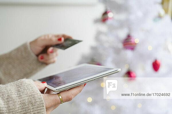 Hände halten Tablet und Kreditkarte neben dem Weihnachtsbaum