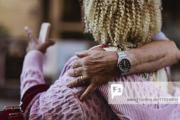 Hand des älteren Mannes um die Frau