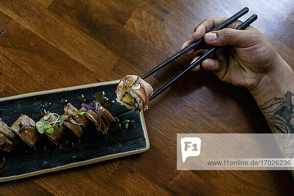 Sushi-Röllchen mit Reis und Fisch  garniert mit frischen Kräutern  auf Essstäbchen