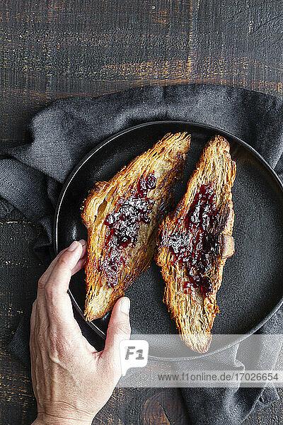 Hand greift nach Croissant mit Kirschmarmelade