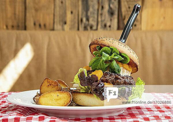 Burger mit Salat und Kartoffeln