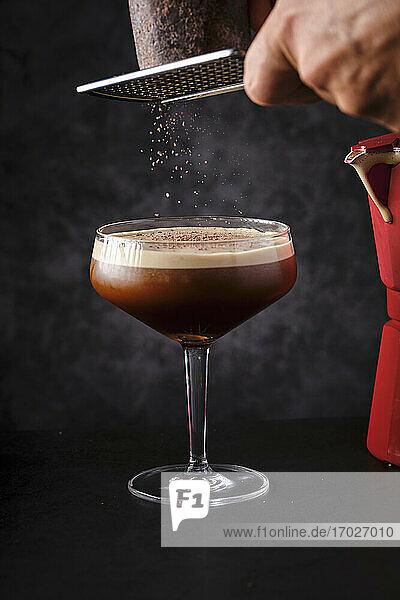 Schokolade auf Kaffeecocktail reiben