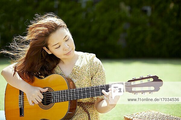 Japanese woman playing guitar in the garden