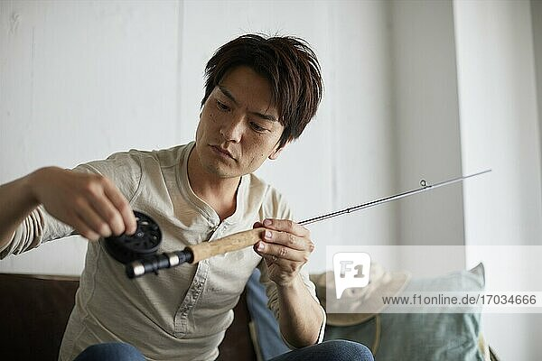 Japanese man cleaning fishing rod at home