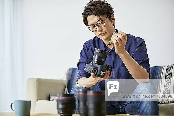 Japanese man cleaning camera at home