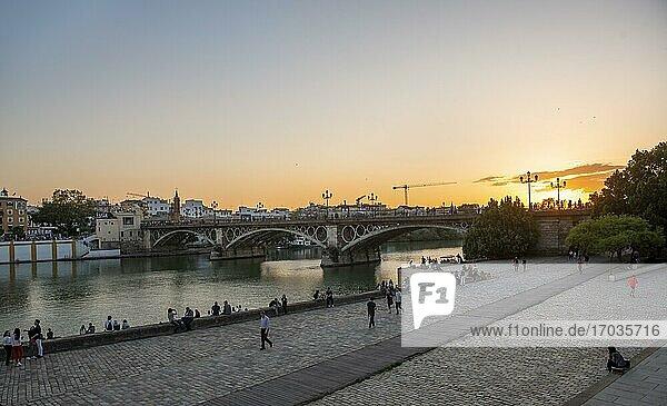 Waterfront Muelle de la sal at the river Rio Guadalquivir with bridge Puente de Triana  sunset  Sevilla  Andalusia  Spain  Europe
