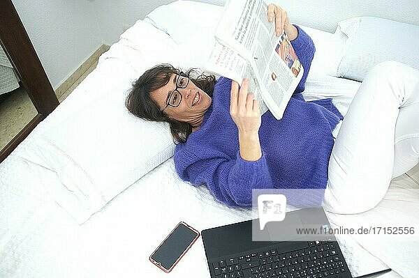 Woman having breakfast with her computer in bed reading a newspaper