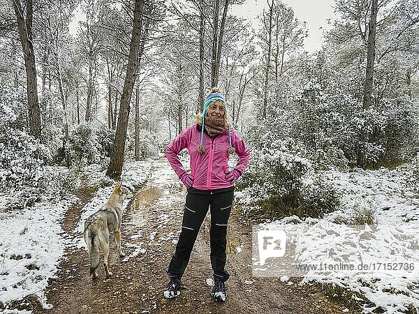 Caucasian young woman with a wolf dog enjoying snow outdoor in a path in a forest area in winter time. Navarre  Spain  Europe.