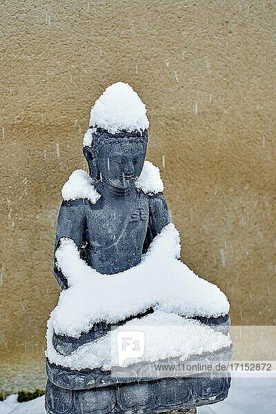 Buddha stony statue under the snow in winter season in a garden.