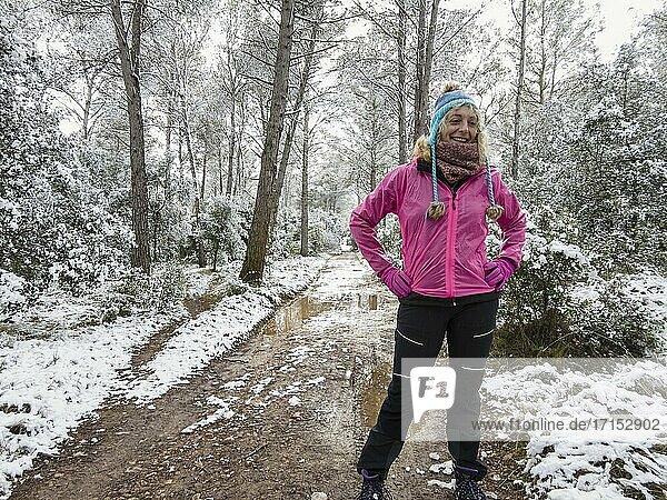 Kaukasische junge Frau mit Hut genießt Schnee im Freien auf einem Weg in einem Waldgebiet im Winter. Navarra  Spanien  Europa.