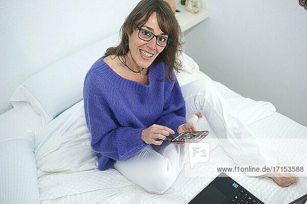 Frau am Morgen im Bett lächelnd und mit ihrem Smartphone hantierend