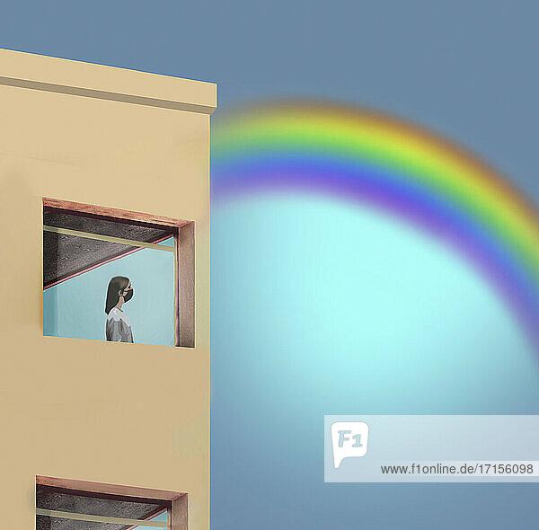 Frau im Lockdown betrachtet Regenbogen durch Fenster