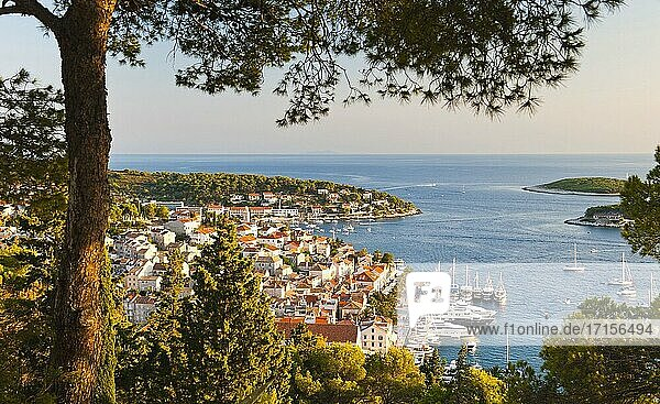 Photo of Hvar Town at sunset  Hvar Island  Croatia  Europe. This photo of Hvar Town and Harbor was taken at sunset from the walk uphill towards Spanish Fort. From the hill above Hvar Town  it provides the best photo oppportunities and views over Hvar Town  Hvar Harbor and Hvar Island  especially at sunset.