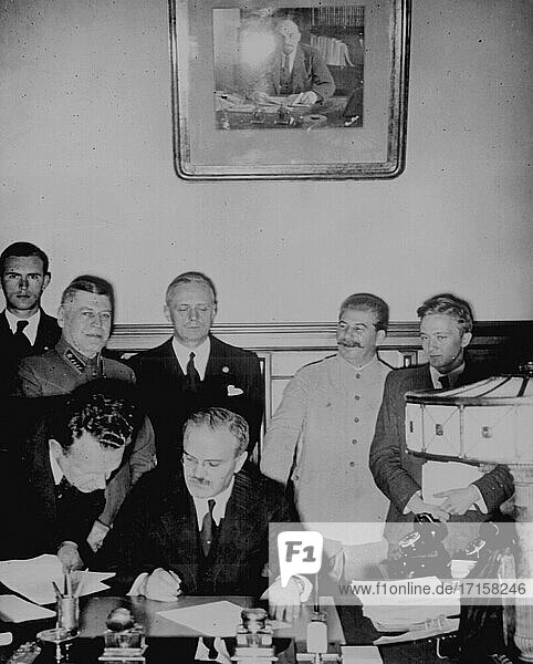 RUSSIA Moscow -- 23 Aug 1939 -- Soviet Foreign Commissar Vyacheslav Molotov signs the German-Soviet nonaggression pact  Joachim von Ribbentrop and Josef Stalin stand behind him. Moscow  August 23. 1939 -- Picture by Lightroom Photos / US Army *Best quality available. NB Not retouched for dust  scratches.