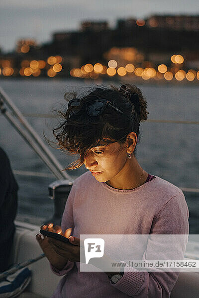 Mid adult woman using smart phone while sitting in boat during sunset