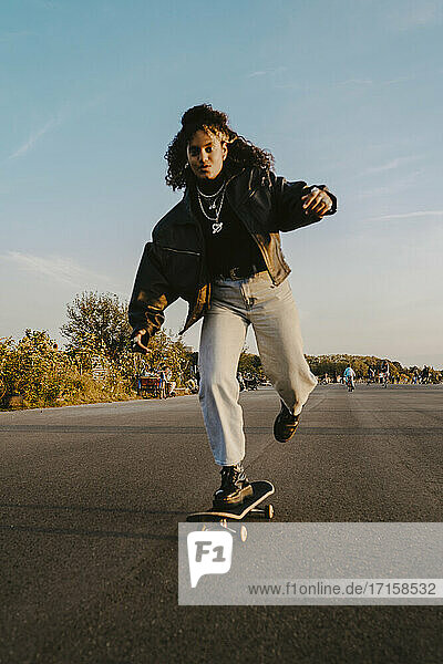 Portrait of cheerful woman skating on road in park