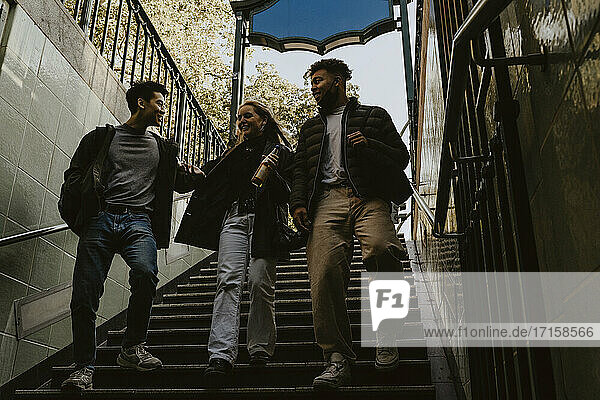 Cheerful friends moving down on steps at subway