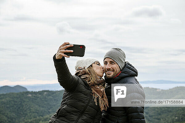 Woman kissing smiling boyfriend while taking selfie against sky during winter