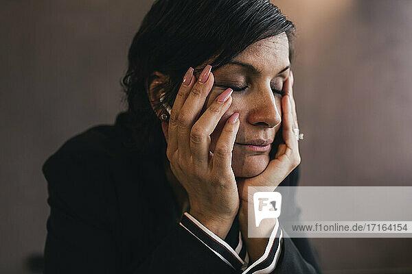 Müde reife Geschäftsfrau mit geschlossenen Augen im Büro