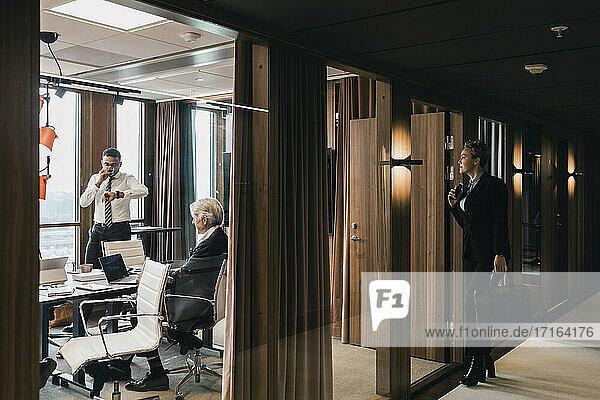 Neugierig Geschäftsfrau Blick auf Kollegen während der Sitzung im Sitzungssaal durch Glaswand