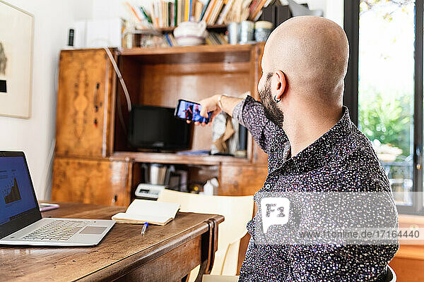 Young man working at home  having video call on phone